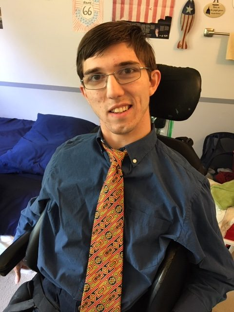 Photo of Will Shawan wearing a blue shirt and orange tie in his dorm room