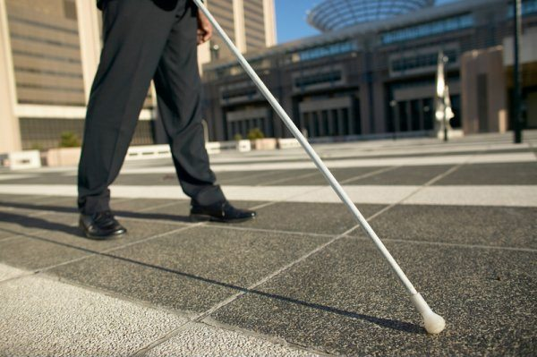 Photo of person wearing black pants and shoes using a white cane outdoors