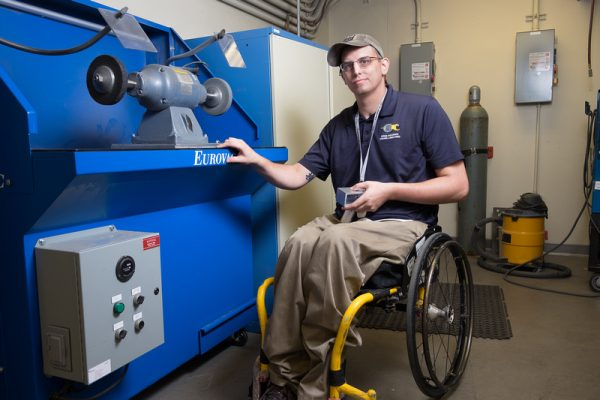 photo of younf man in a wheelchair using an industrial machine