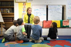 Photo of blind woman reading to children.