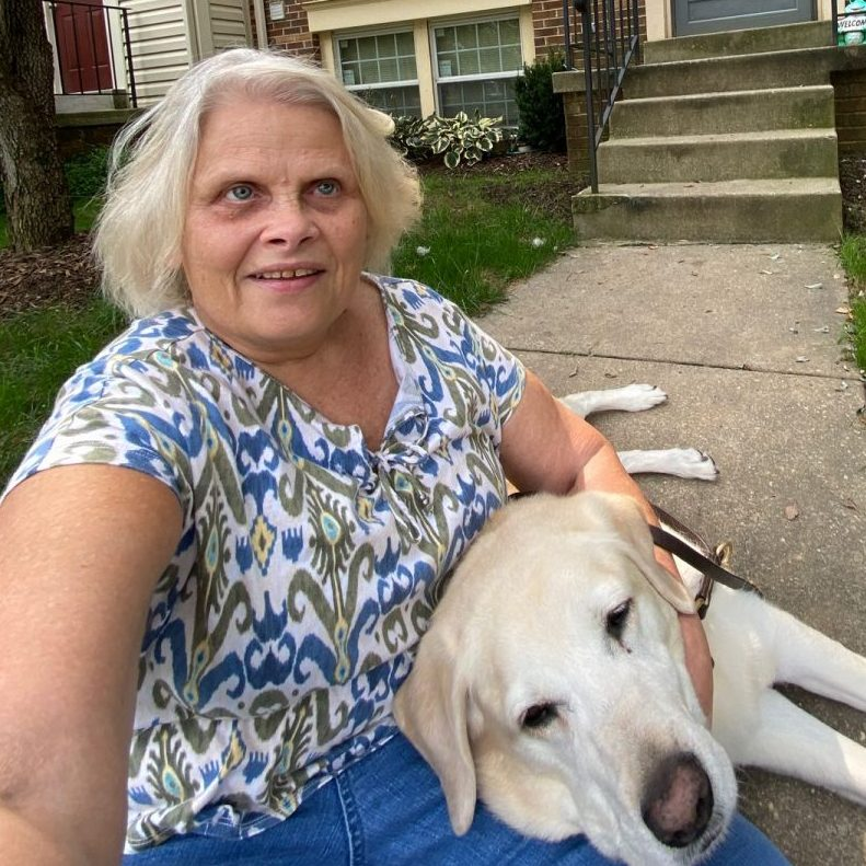 Photo of Cindy LaBon sitting outside with her service dog, Gardenia.