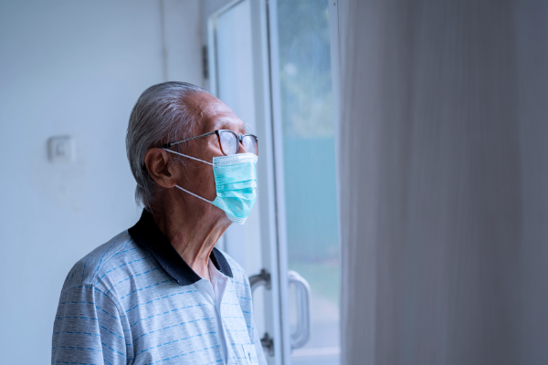 Older person wearing a face mask looking out a window