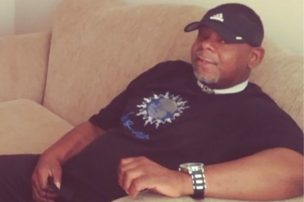 Photo of shelton forte sitting on couch smiling, wearing a black baseball cap and black shirt.