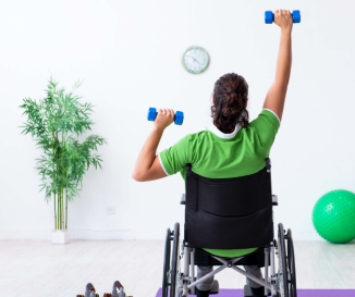 Photo of a wheelchair user in green shirt using blue handweights on a white background.
