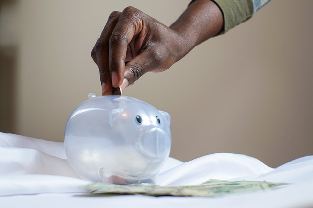 Photo of hand putting money in a piggy bank.