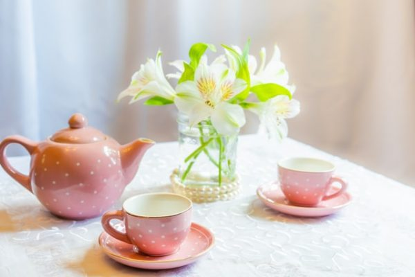 photo of table with white lace tablecloth, a pink polka dot tea set, and a vase of white lilies.