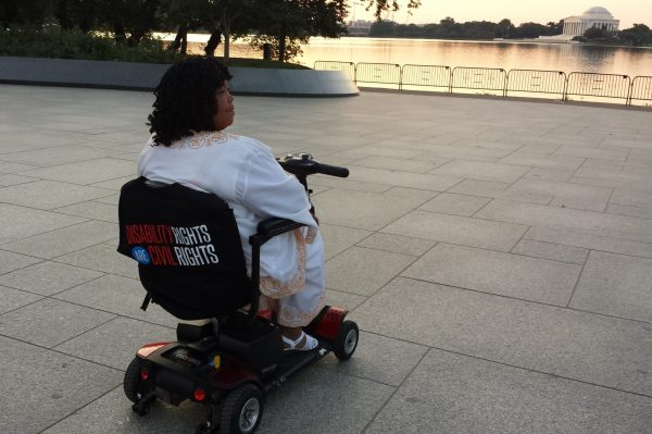 Photo of deborah jackson in motorized wheelchair in front of the washington dc reflecting pool at dusk.