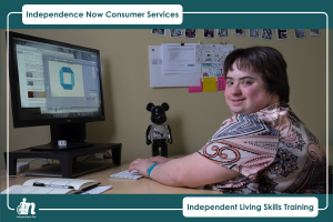 Graphic with Green and white border with text that says Independence Now Consumer Services. Independent Living Skills training. Photo in center of person with disability using a computer.