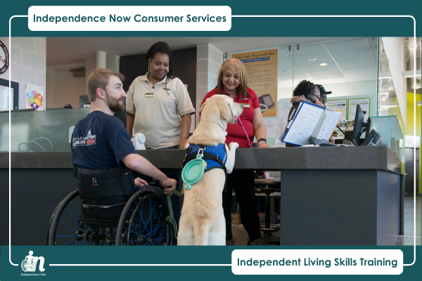 Photo of man in wheelchair with service dog at service desk with two women looking at dog and smiling.