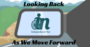 "Graphic of independence now logo appearing in a rearview mirror of a car that is driving forward. Black text that says ""Looking back as we move forward."""