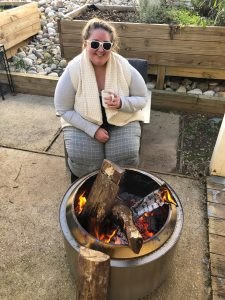 Photo of Nina Russel wearing a soft white sweater and holding a mug of hot cocoa while sitting near a stainless steel firepit.