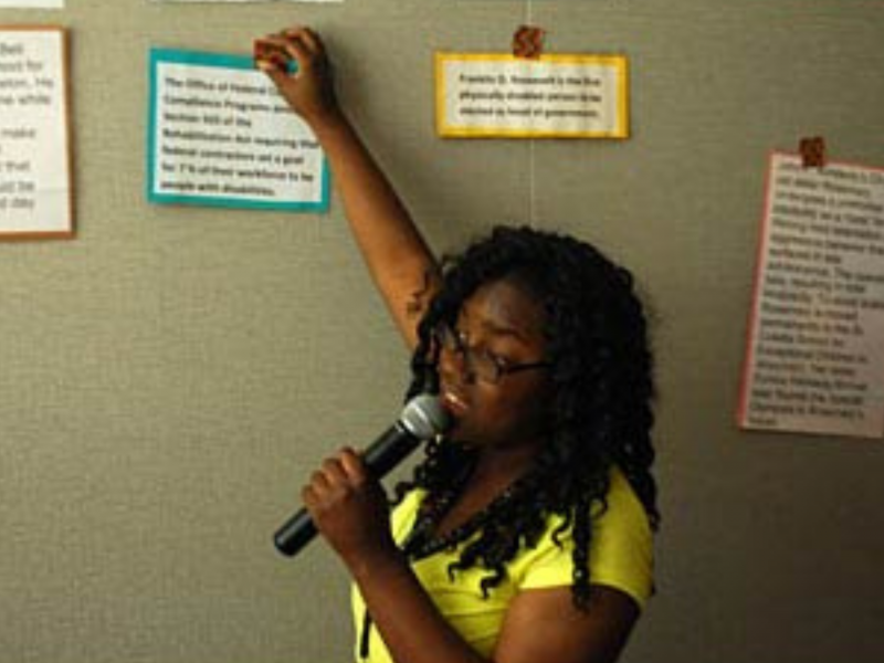 Photo of young woman holding a microphone in front of a wall with a disability history timeline.