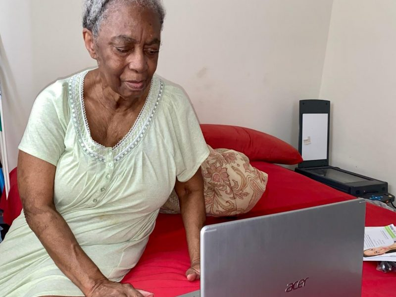 Photo of Ms. Annette on her bed using her new laptop.