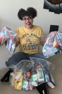 """Photo of Kayla, a young black woman, wearing black rimmed glasses and dark lipstick. She is wearing jeans and a yellow shirt that say's Let's keep our planet clean."""" She is sitting on the floor holding plastic bags filed with toiletries."""