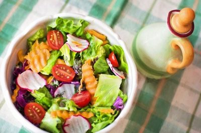 Photo of salad bowl with a variety of colorful vegetables on a green and pink plaid tablecloth.