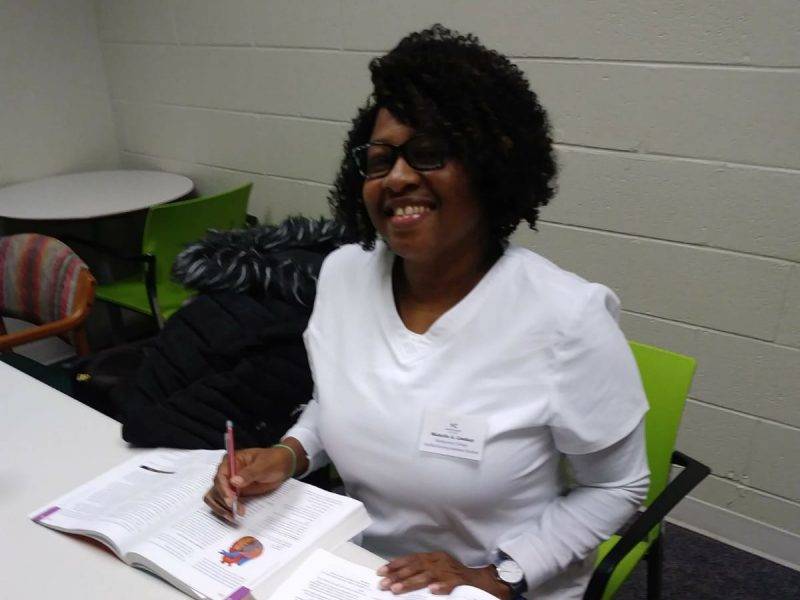 Photo of Michelle Lindsay in a white nurses uniform studying for her certified nursing assistant exam.