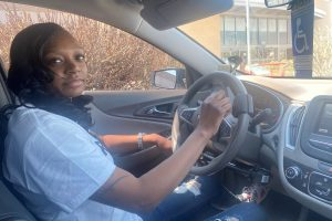 Independence Now consumer danesha sitting in the driver's seat of her modified vehicle.
