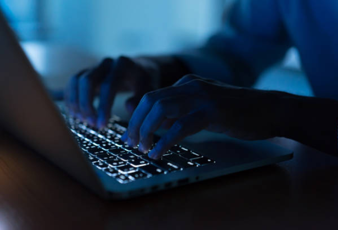 Photo of person's hands on a laptop in dark blue light.