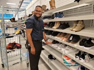 Photo of young man wearing a blue polo working in a shoe store standing in front of a large shoe rack.