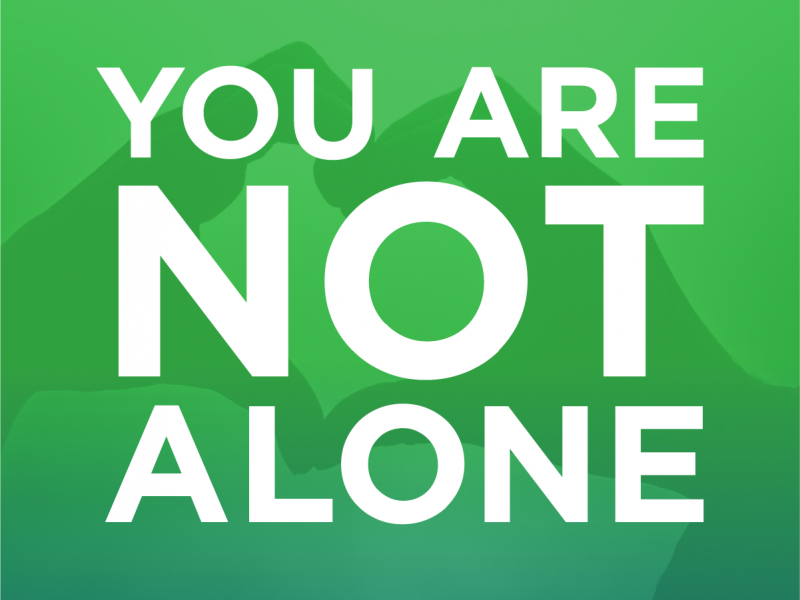 """Green graphic with photo of hands in the shape of a heart with words in white text that say """"You are not alone."""