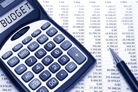 """Photo of a calculator with the word """"budget"""" appearing on the screen on top of a spreadsheet."""
