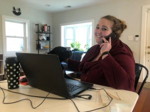 photo of nina russell in her home office using a laptop and a smartphone to speak with a consumer during covid-19 quarantine.