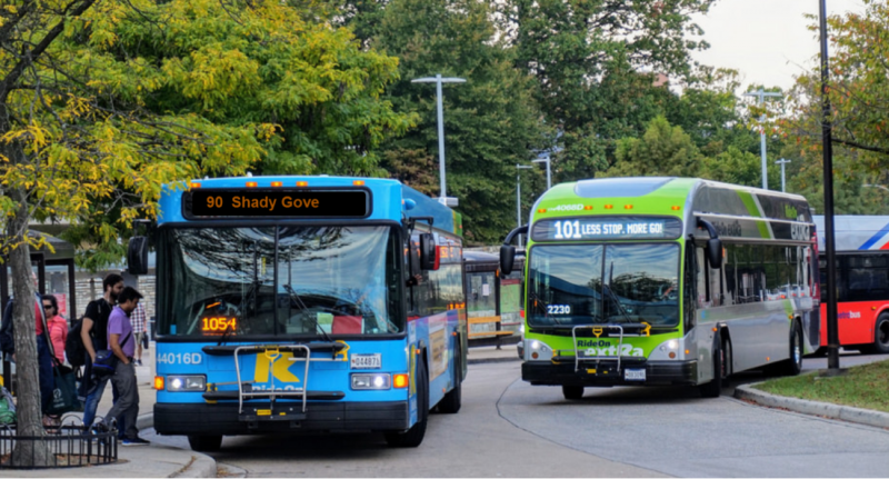 Photo of a blue public transit bus followed by a green public transit bus at a bus stop.
