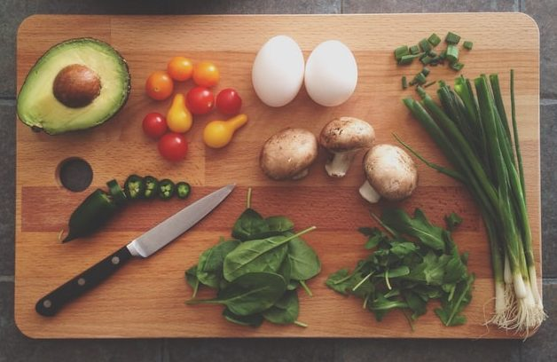 Photo of curring board with avocado, cherry tomatoes, eggs, mushrooms, peppers, scallions, and herbs.