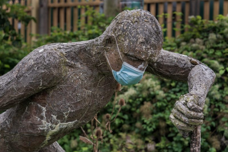 Photo of a sculpture of a man, with a mask added, making the artwork even more powerful, in the current pandemic, with many suffering loss and mental health issues.