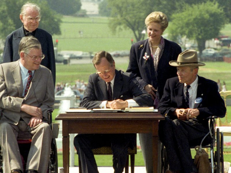 Photo of President George H. W. Bush signing the Americans with Disabilities Act into law. Pictured (left to right): Evan Kemp, Rev Harold Wilke, Pres. Bush, Sandra Parrino, Justin Dart.
