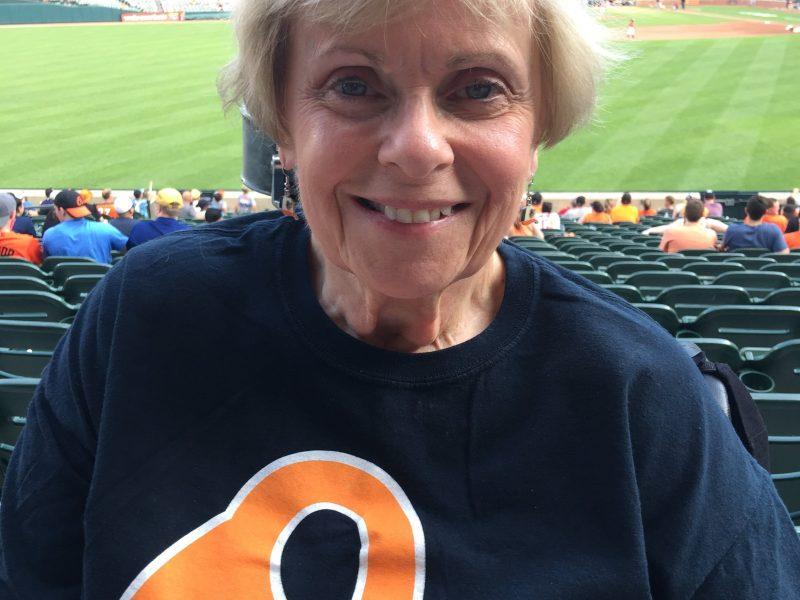 Photo of Cathy Raggio in Orioles baseball tee shirt at Camden Yards stadium.