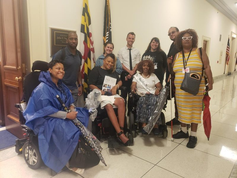 Photo of group of disability advocates outside the office of a federal elected official representing the state of maryland. One delegate is Miss Wheelchair maryland.