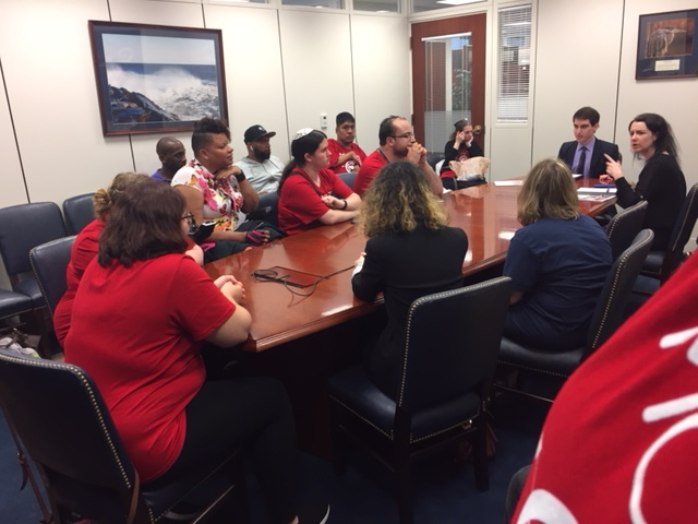 Photo of group of disability advocates sitting at a large conference table with a federal elected official representing the state of maryland.