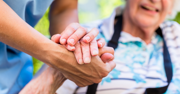photo of a professional careviver holding the hand of an older person who is smiling.