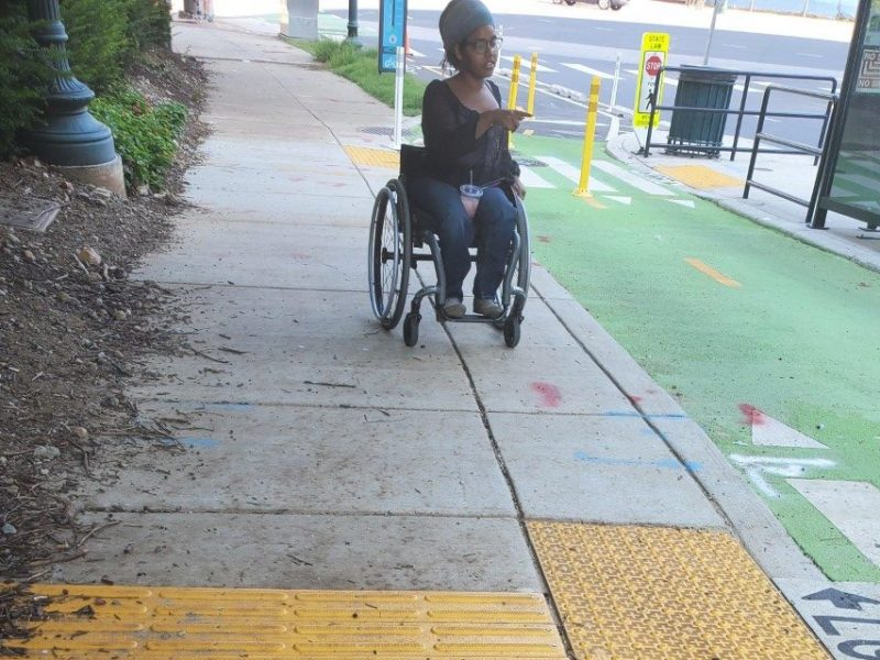 Photo of wheelchair user examining a floating bus stop.