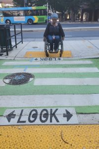 Photo of wheelchair user crossing the road to access a floating bus stop.