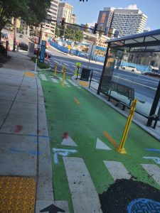 Photo of a floating bus stop with the sitting area of the stop separated from the sidewalk with a bicycle roadway..
