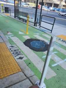 """Photo of a floating bus stop with the sitting area of the stop separated from the sidewalk with a bicycle roadway WITH THE WORK """"LOOK"""" PAINTED ON IT."""