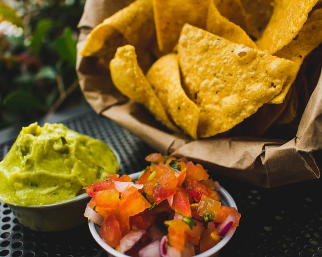Photo of tortilla chips wth fresh salsa and guacamole.