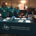 Photo of Sarah Basehart; Denise Sosbe; Cindy LaBon and her guide dog, Gardenia; Shannon Minnick, all wearing matching teal polo shirts and standing behind the Independence Now table at the 2018 DORS conference.