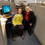 Photo of Denise Sosbe and Nicole sitting in a cubical with their arms around each other.