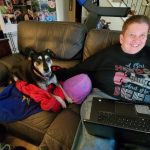 Photo of Denise Sosbe with her dog working from home during COVID.