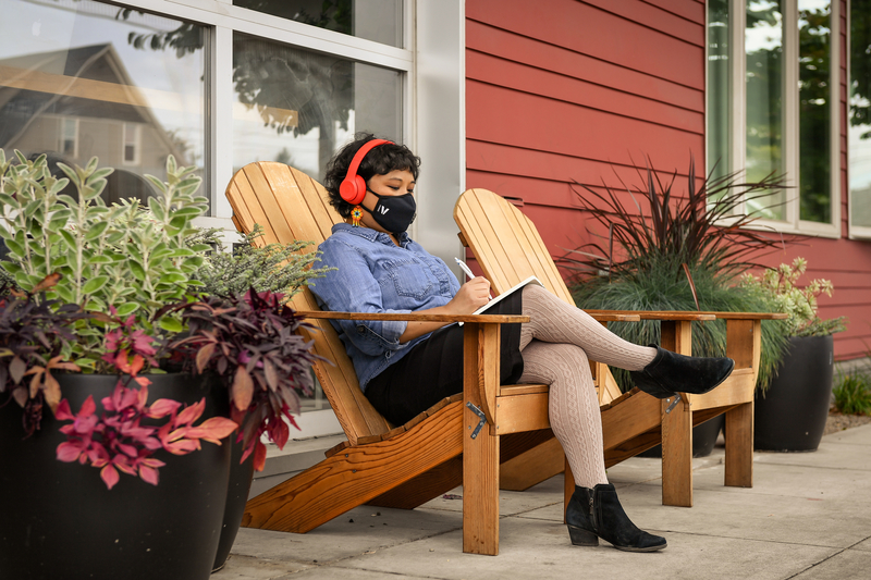 A Filipinx woman with a filtering face mask sits outside a cafe and writes in a notebook. She is wearing headphones and in front of a window, with potted plants all around.