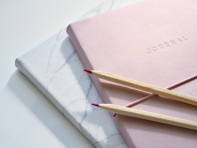 Photo of pink jurnal on white marble background with red colored pencils.