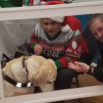 Photo of Denise Sosbe holding an Independence Now frame with Cindy Labon and her guide dog, Gardenia, at the Independence Now office holiday party. Cindy is wearing a Santa hat and festive sweater.