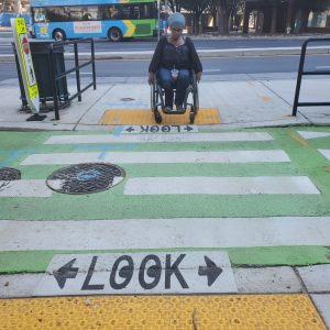 """Photo of Serena Jaros, a wheelchair user, attempting to use a floating bus stop in Montgomery County, Maryland. In order to access the bus stop she has to cross into traffic at a cross walk with the word """"Look"""" painted on the ground."""