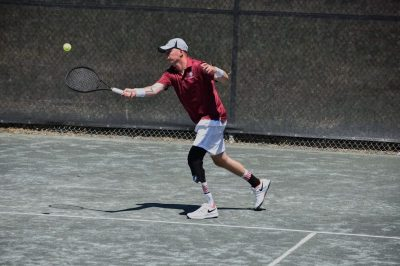 Photo of Damian Wright, an amputee missinf his right leg, playing tennis